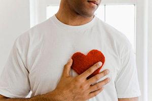 Мужчина держит руку на сердце
