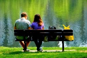 мальчик с девочкой сидят на лавке возле реки