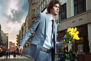 мужчина в костюме с букетом желтых тюльпанов