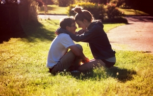 парень с девушкой сидят на траве