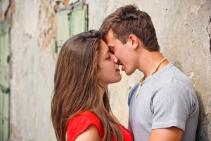парень с девушкой возле стены дома