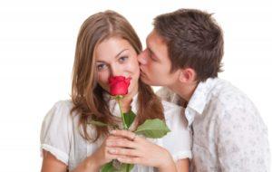 девушка нюхает красную розу а парень ее целует