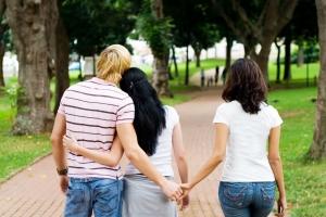 парень гуляет с двумя девушками в парке