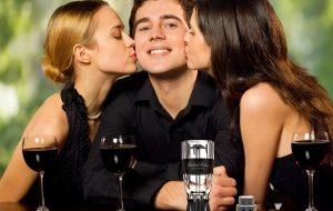 две девушки целуют парня