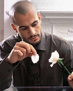 мужчина отрывает лепестки белой розы