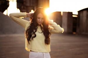 девушка трогает свои волосы на закате
