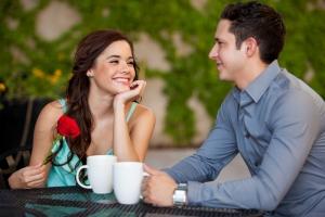 парень держит белую чашку а девушка красную розу