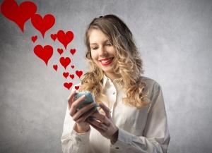 девушка держит телефон из которого вылетают сердечки