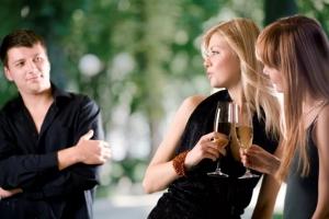 две девушки смотрят на мужчину в черном