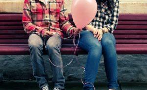 парень держит воздушный шарик и сидит с девушкой на лавке