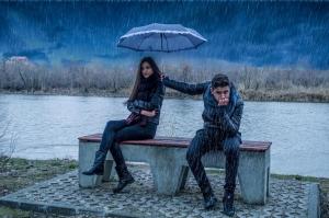 парень держит зонт над девушкой под дождем