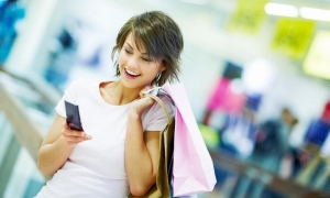 девушка держит телефон и покупки