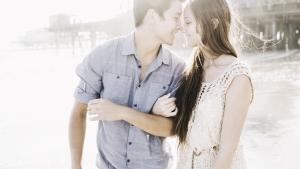 парень с девушкой идут под руку по берегу