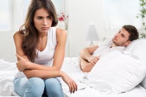 мужчина лежит в кровати а женщина возле него сидит
