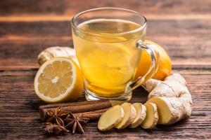 чай в чашке с кусочками имбиря и лимоном