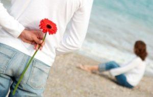 парень держит красный цветок