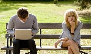 мужчина с ноутбуком и женщина сидят на лавке