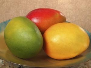 три манго на тарелке
