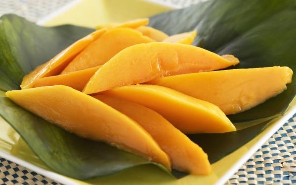 ломтики манго на листьях