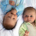 два малыша лежат на кровати