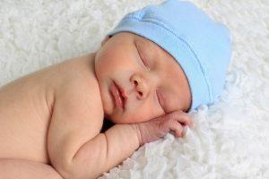 новорожденный малыш в голубой шапочке
