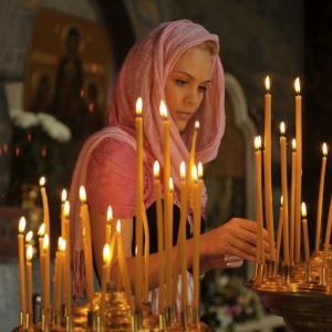 девушка ставит свечу в церкви