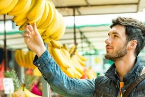 мужчина выбирает бананы