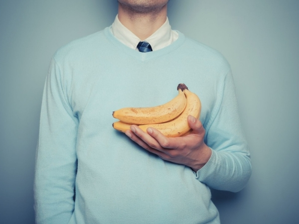 мужчина держит ветку бананов