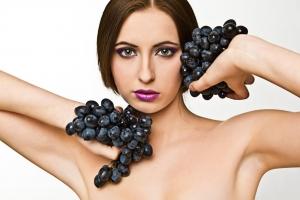 женщина держит черный виноград