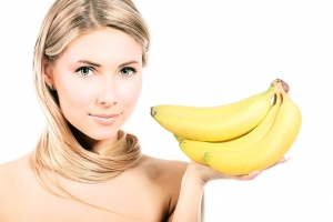девушка держит ветку бананов