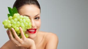 женщина держит у лица виноград