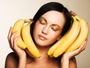 женщина держит ветки бананов