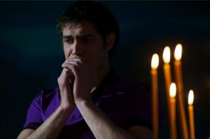 мужчина молится у свечей