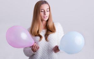 женщина держит в руках голубой и розовый шарики