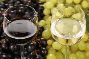 бокалы с белым и красным вином и виноград