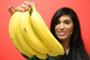 женщина держит связку бананов