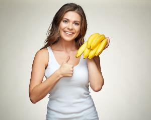 женщина держит ветку бананов и показывает класс