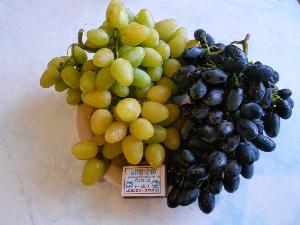 гроздь белого и синего винограда на тарелке