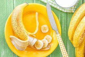 нарезанные бананы на желтой тарелке и нож