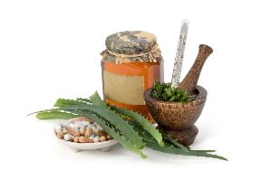 листья алоэ, банка с медом, капсулы и ступка
