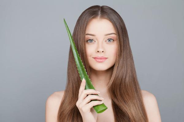 девушка с длинными волосами держит лист алоэ