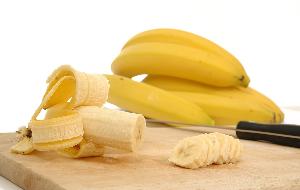 целые и нарезанные бананы с ножом на доске