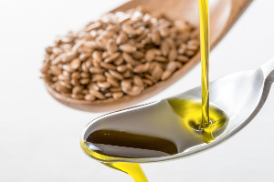 масло льют в ложку и семена льна в ложке