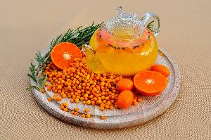 стеклянный чайник, облепиха и апельсин на деревянной подставке