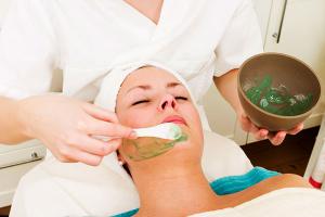 женщине наносят маску на лицо