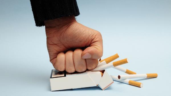 кулак мнет пачку с сигаретами