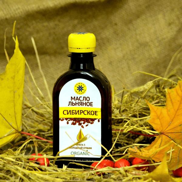 льняное масло в бутылке, кленовые листья и красные ягоды на ветках