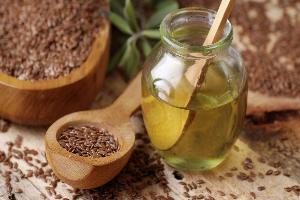 семена льна в деревянной ложке и льняное масло в стеклянной баночке