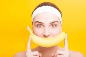девушка держит банан у лица как улыбку