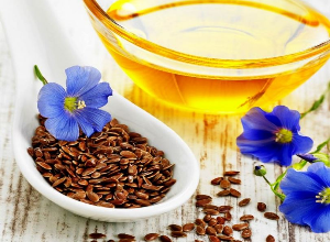 цветки, масло и семена льна в ложке